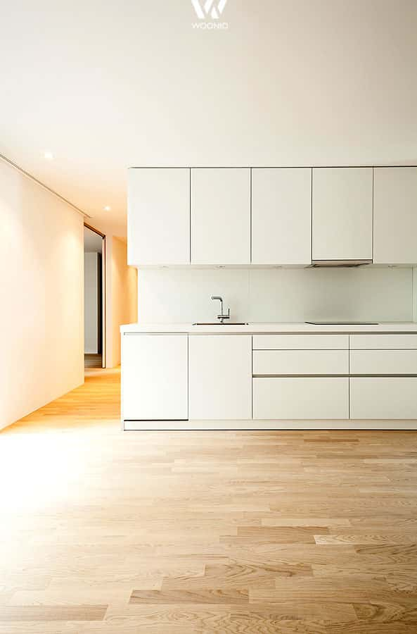 Die weißen Küchenfronten ergänzen sich gut mit dem natürlichen ...